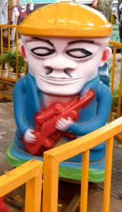 Children's merry-go-round character, complete with sub-machine gun
